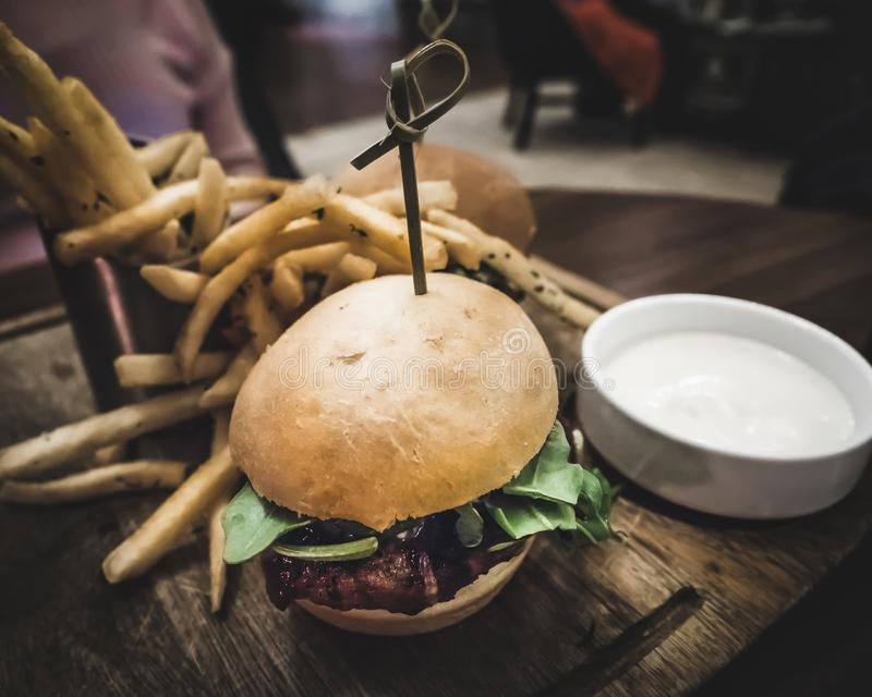 Burger and Fries on Wood Plate royalty free stock photos