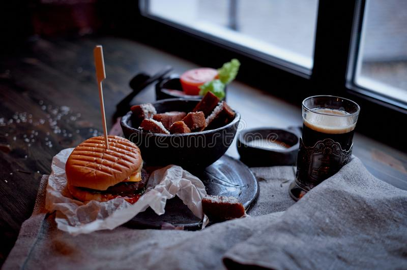 Burger with garlic croutons in the dark interior of the pub. Hearty, quick lunch.Atmospheric photo. Dark beer. Burger with garlic croutons in the dark interior stock photo