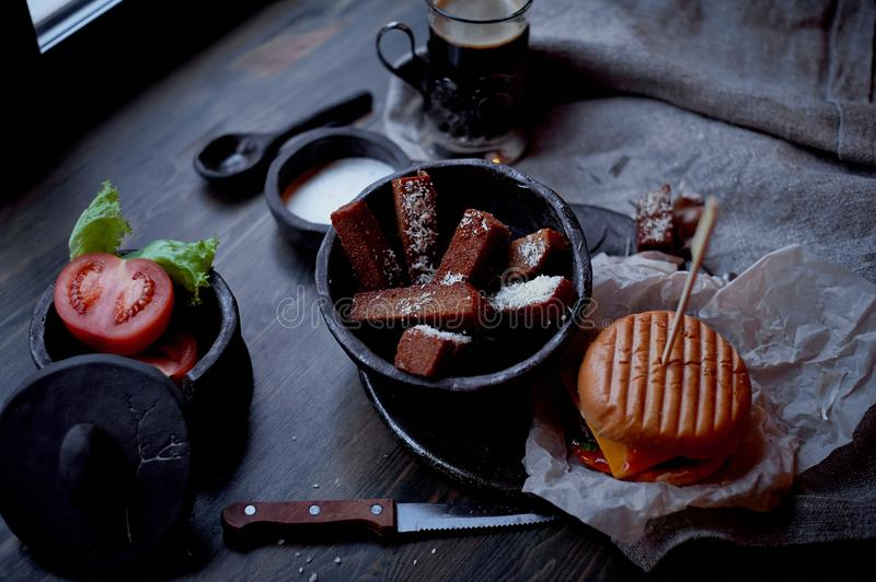 Burger with garlic croutons in the dark interior of the pub. Hearty, quick lunch.Atmospheric photo. Burger with garlic croutons in the dark interior of the pub royalty free stock photography