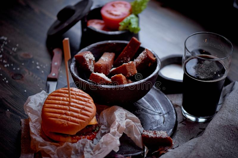 Burger with garlic croutons in the dark interior of the pub. Hearty, quick lunch.Atmospheric photo. Dark beer. Burger with garlic croutons in the dark interior stock photos