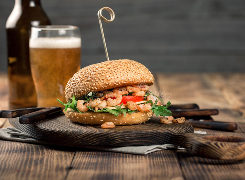 Burger with grilled shrimp and light beer. On a wooden table stock images