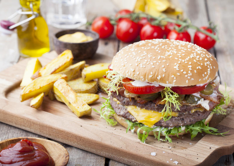 Burger, hamburger with frech fries, ketchup, mustard and fresh vegetables royalty free stock image