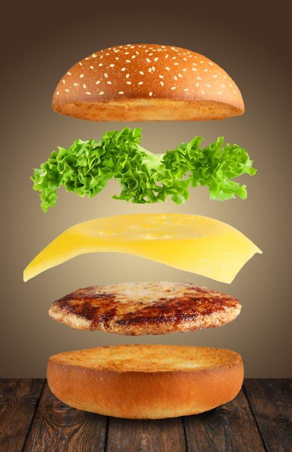Burger ingridients separated flying in air. Burger ingredients. Burger layers . Separated burger ingredients at wood. Hamburger explosion. Cheeseburger flying royalty free stock photo