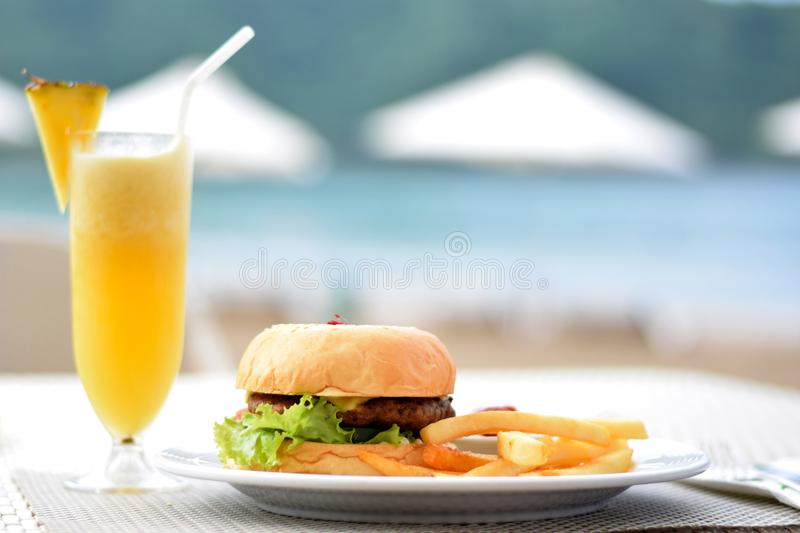 Burger With Lettuce and Fries on Plate Beside Pineapple Juice stock photography