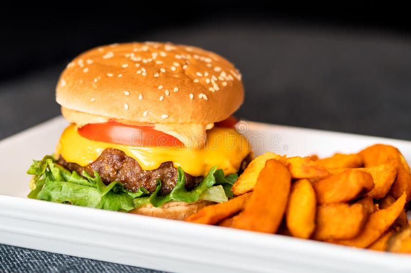 Burger meal on plate. Delicious hamburger with juicy beef, melting cheddar cheese served with crispy sweet potato fries. Home cooking or restaurant dinner royalty free stock photography