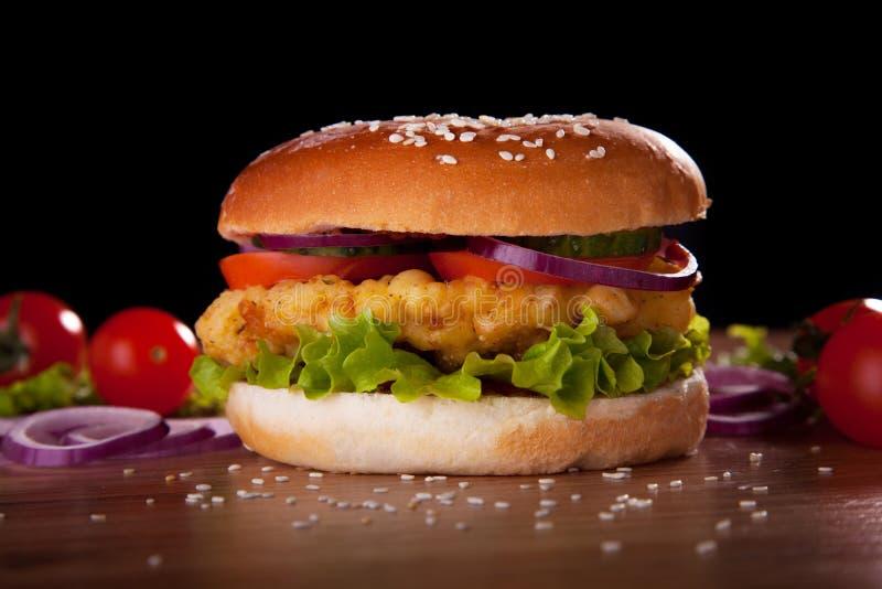 Burger mit Huhn, Salat, Gurken, Tomaten und Zwiebeln stockfoto