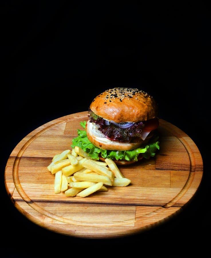 Burger mit Pommes-Frites auf einem hölzernen Brett Geschossen in einem Studio lizenzfreie stockfotos