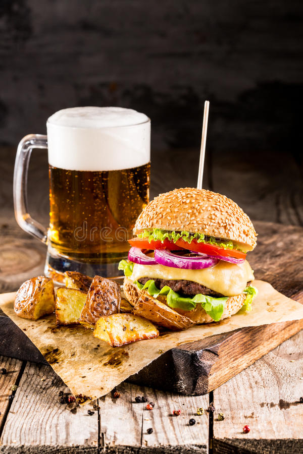 Burger mit Rindfleisch und gebratene Kartoffeln und Glas kaltes Bier stockfoto