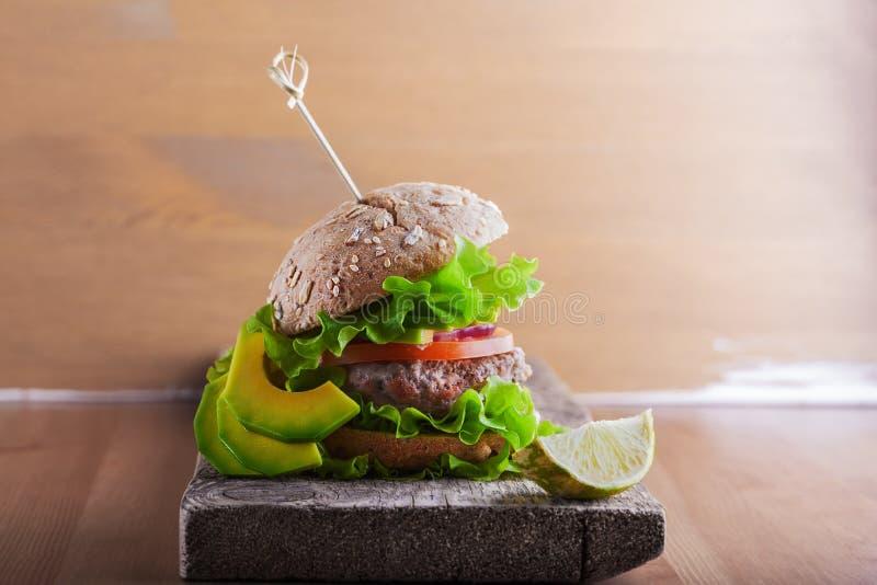 Burger mit Salat, Zwiebel lizenzfreie stockfotos