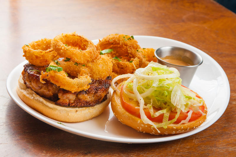 Burger and Onion Rings. Gourmet Burger with Onion Rings, lettuce and mustard royalty free stock images