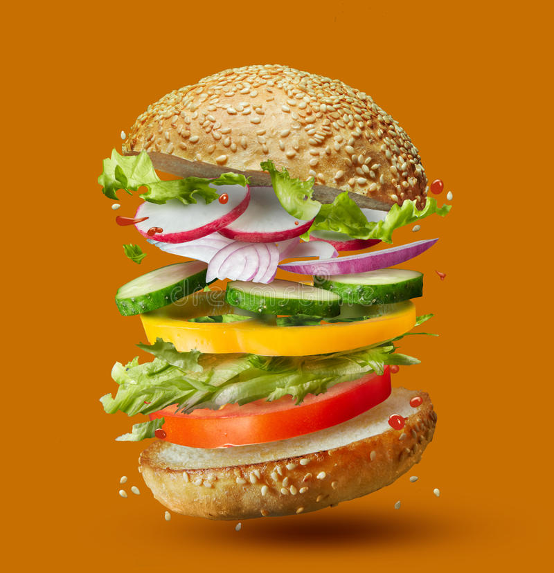 Burger preparation ingredients falling into place royalty free stock images