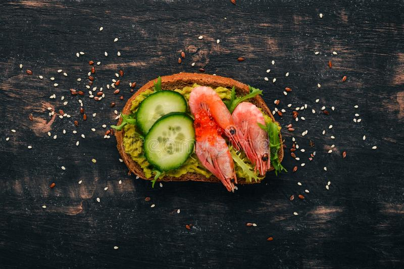 Burger, sandwich with shrimp, avocado, caviar and cucumber. On a wooden background. stock photos