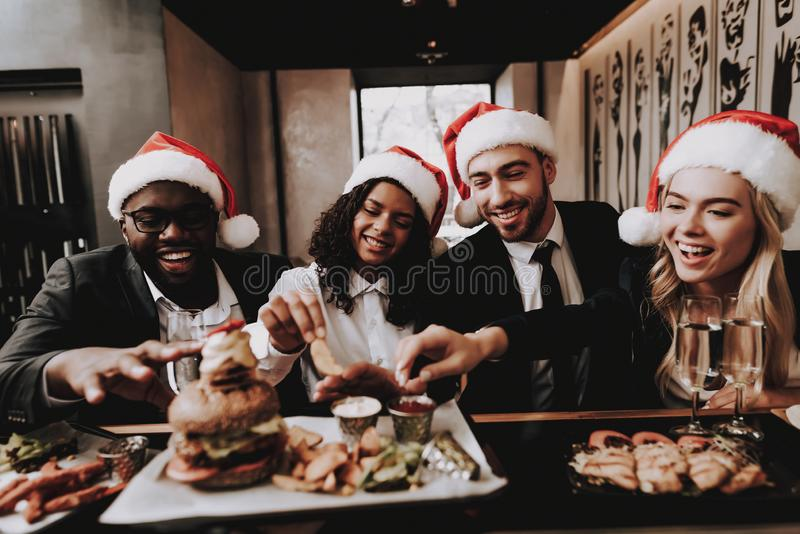 Burger. Santa`s Hat. Drink Alcoholic Beverages. Burger. Santa`s Hat Drink Alcoholic Beverages. Girls and Guys Young People. Rest. Different Races Communicate royalty free stock photo