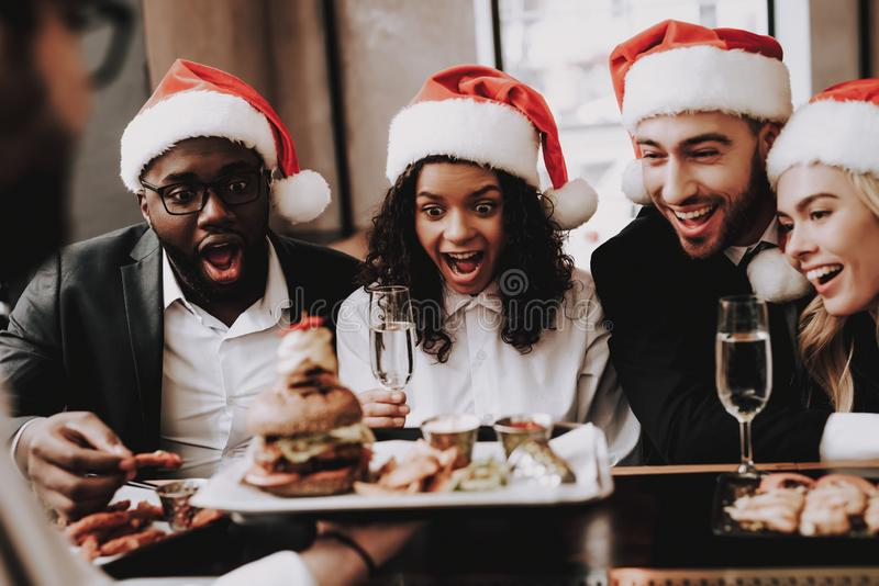 Burger. Santa`s Hat. Girls and Guys. Young People. stock photos