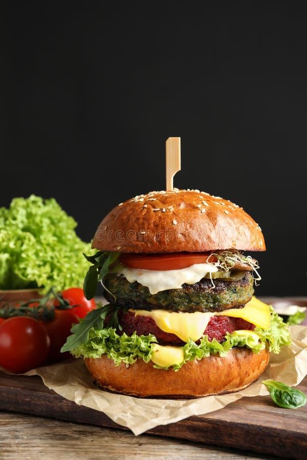 Burger und Gemüse des strengen Vegetariers auf Tabelle gegen dunklen Hintergrund stockbild