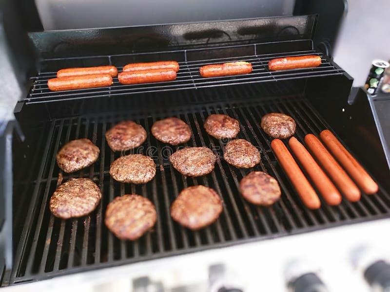 Burger und Hotdoge auf dem Grill lizenzfreie stockfotografie