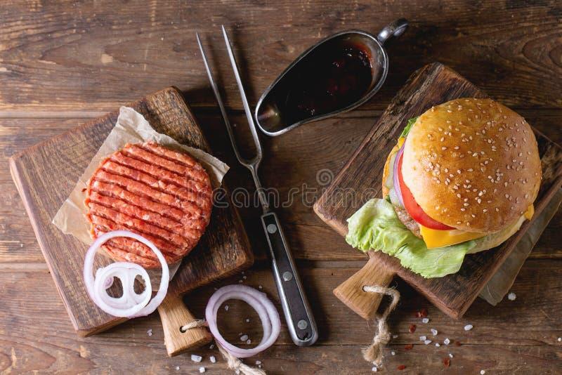 Burger und rohes Kotelett stockfotos