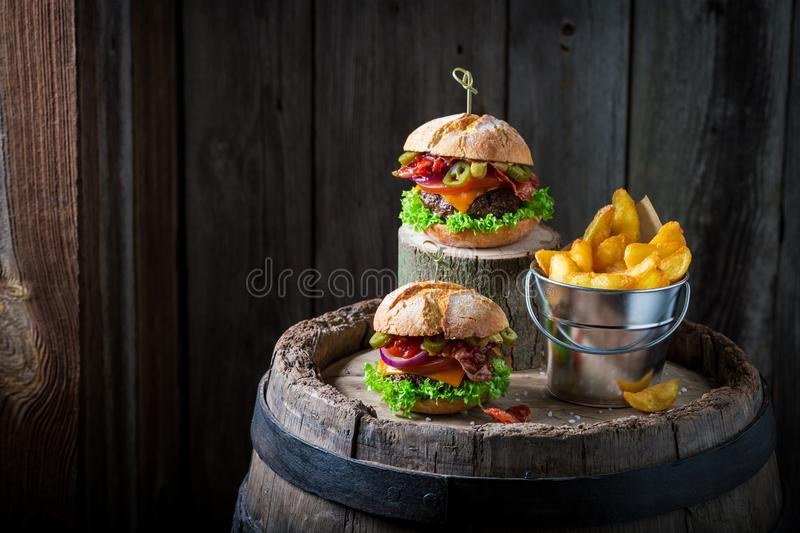 Burger with vegetables, beef and pepperoni served with chips stock image