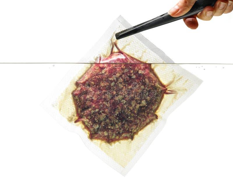 Burgerfleisch im Vakuumbeutel im Wasser; lokalisiert auf Weiß stockbild