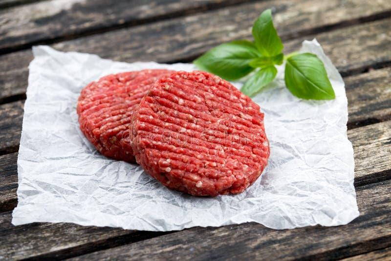 Burgers εγχώριου χειροποίητα κομματιασμένα βόειου κρέατος που διακοσμούνται με το βασιλικό σε τσαλακωμένο χαρτί πίνακας ξύλινος στοκ φωτογραφίες με δικαίωμα ελεύθερης χρήσης
