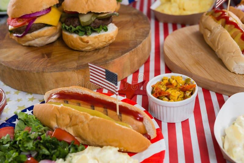 Burgers και χοτ-ντογκ στον ξύλινο πίνακα με το θέμα στις 4 Ιουλίου στοκ φωτογραφίες