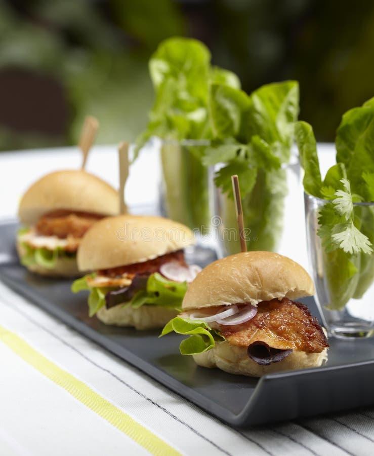 Burgers κοτόπουλου στον πίνακα στοκ εικόνα