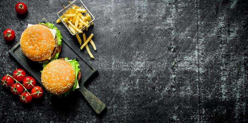 Burgers με τα τηγανητά και τις ντομάτες στοκ εικόνες