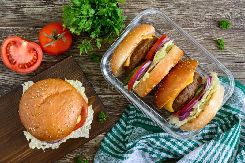 Burgers με juicy cutlet, φρέσκα λαχανικά, τριζάτο κουλούρι με τους σπόρους σουσαμιού σε έναν ξύλινο πίνακα Παραδοσιακό γρήγορο φα στοκ εικόνες