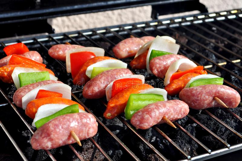 Burgers, Beef and Sausages on a grill with flames stock photos