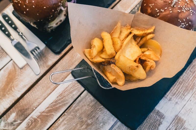 Burgers de vegetais com sementes de sésamo e batatas fritas caseiras Comida rápida deliciosa para vegans em madeira imagens de stock royalty free