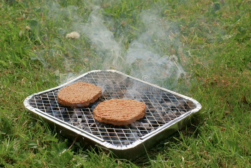 Burgers On Disposable Barbeque Royalty Free Stock Photos