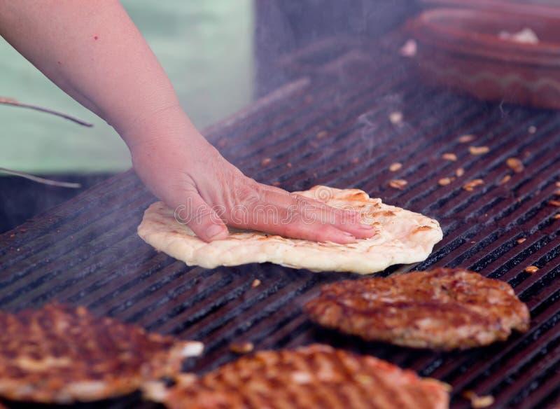 Burgers en vlak brood op barbecue stock foto