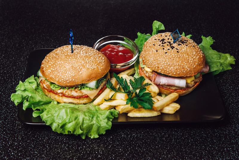 Burgers and French Fries Fast Food. On a tray and on a black background stock images