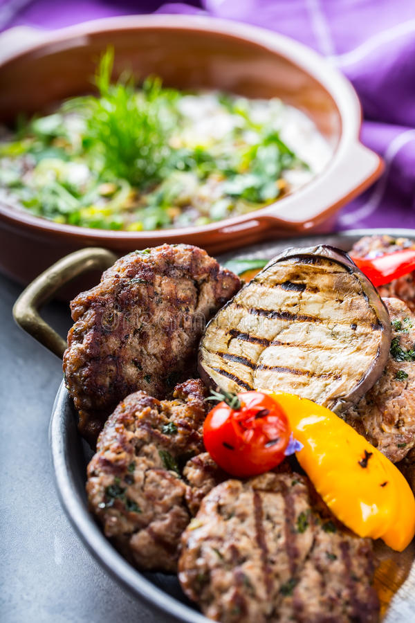 Burgers. Grill burgers. Minced burgers. Roasted burgers with grilled vegetable and herb decoration. Minced meat grilled in a hotel stock photo