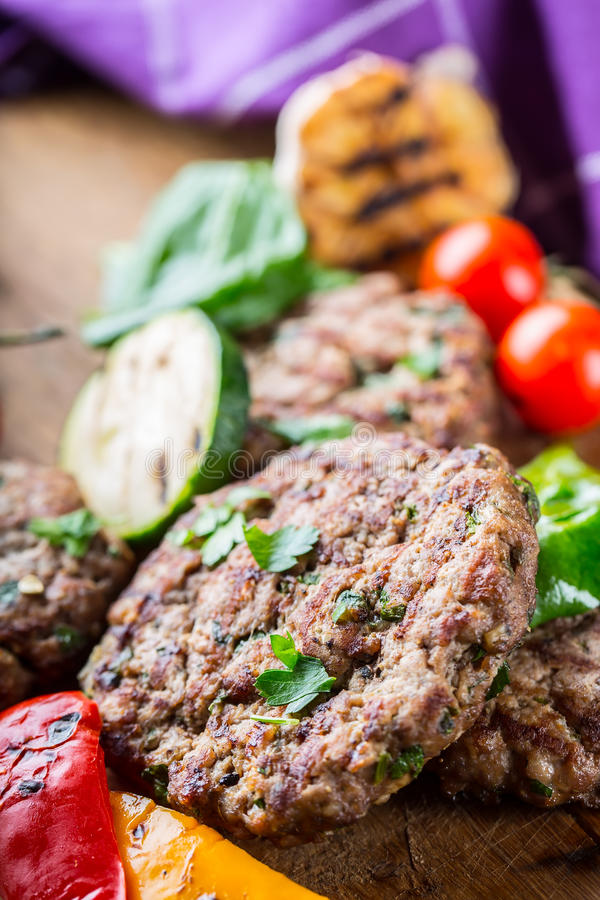 Burgers. Grill burgers. Minced burgers. Roasted burgers with grilled vegetable and herb decoration. Minced meat grilled in a hotel royalty free stock photo