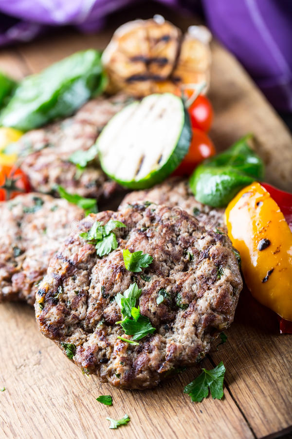 Burgers. Grill burgers. Minced burgers. Roasted burgers with grilled vegetable and herb decoration. Minced meat grilled in a hotel royalty free stock photography