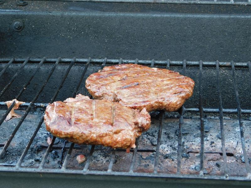 Burgers on the grill royalty free stock photography