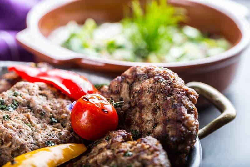 Burgers Grillburgers Fijngehakte burgers Geroosterde burgers met geroosterde groente en kruiddecoratie Gehakt in een hotel wordt  stock afbeeldingen