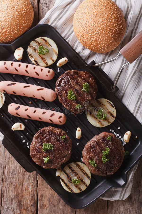 Burgers and hot dogs on the grill pan closeup. vertical top view. Grilled hamburgers and hot dogs on the grill pan closeup. vertical top view royalty free stock images