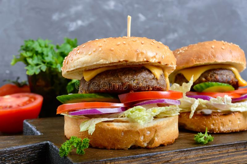 Burgers with juicy cutlet, fresh vegetables, crispy bun with sesame seeds on a wooden table. Close-up. royalty free stock images