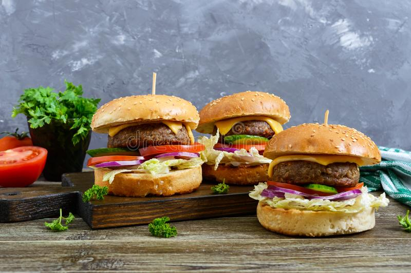 Burgers with juicy cutlet, fresh vegetables, crispy bun with sesame seeds on a wooden table. stock photos