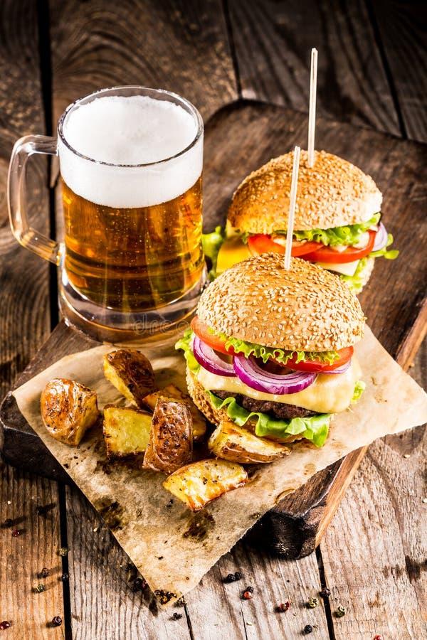 Burgers met rundvlees en gebraden aardappels en glas koud bier stock afbeeldingen