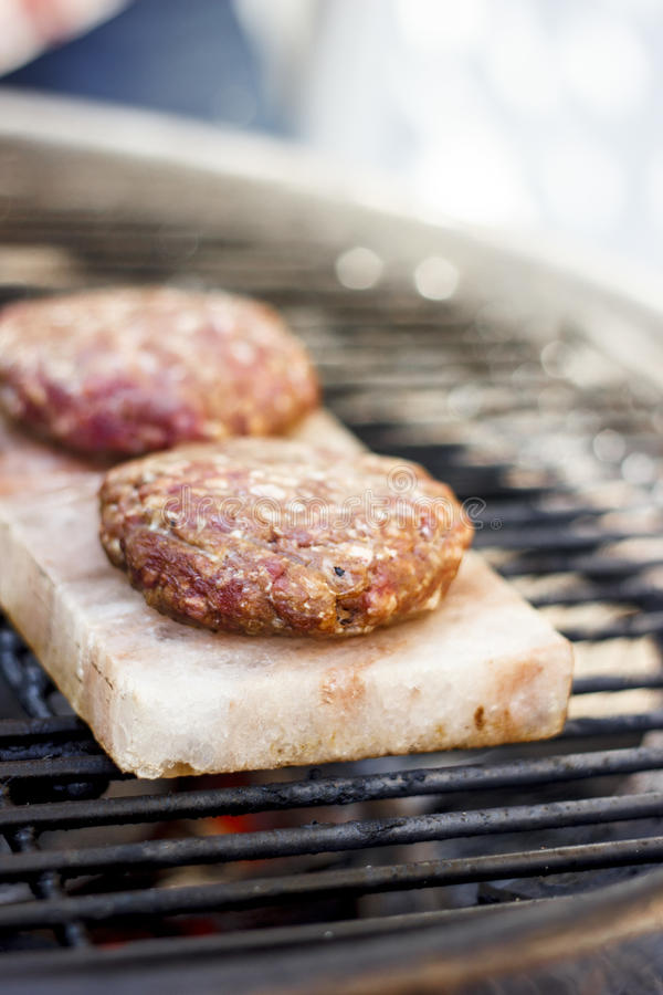 Burgers on salt plate. Grilling burgers on salt plate royalty free stock images