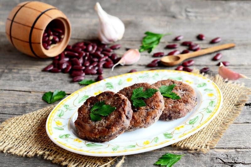 Burgers van gekookte en fijngestampte rode bonen op een plaat wordt gemaakt die Verspreide ongekookte rode bonen, knoflook, verse stock foto's