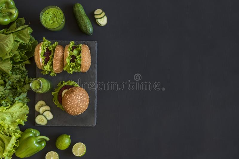 Burgers Vegan με cutlet τεύτλων και πράσινοι καταφερτζήδες στο μαύρο υπόβαθρο Υγιή vegan τρόφιμα Διατροφή Detox Επίπεδος βάλτε με στοκ εικόνες