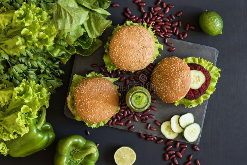 Burgers Vegan με cutlet τεύτλων και πράσινοι καταφερτζήδες στο μαύρο υπόβαθρο Υγιή vegan τρόφιμα Διατροφή Detox Επίπεδος βάλτε στοκ εικόνες