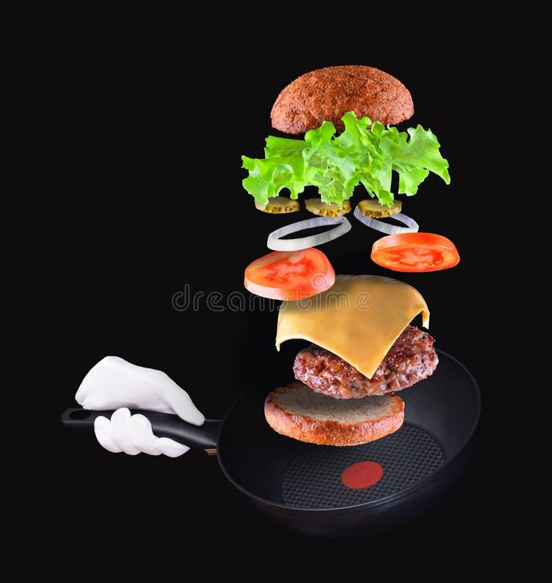 Burgerteilfliegen in einer Luft auf Schwarzem Hand, die Bratpfanne h?lt stockfotografie