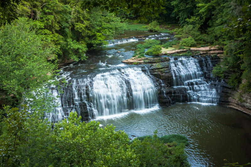 Burgess Falls Cascading sobre Gray Rocks escuro, cercado por árvores verdes fotos de stock royalty free