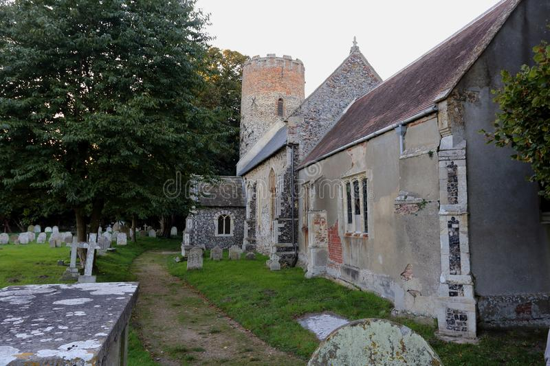 Burgh Castle church in Norfolk. England, with its flint construction and unusual circular tower which is a feature of many ancient churches in the county of stock images