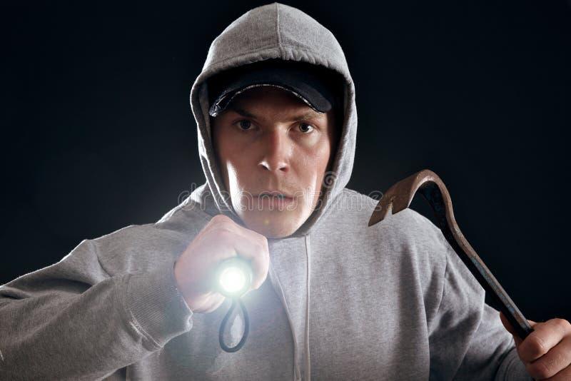 Burglar. With crowbar and a flashlight ready for work stock photo